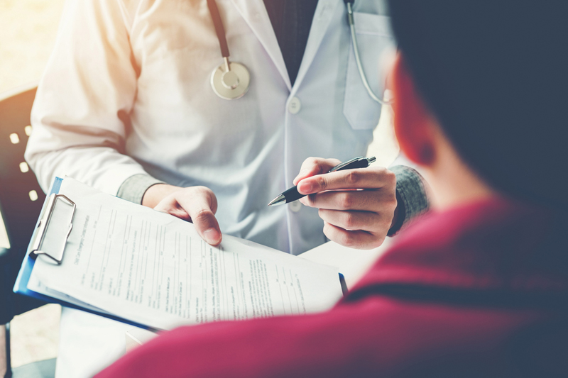 doctor holding forms out for patient to sign