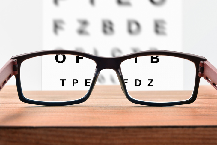 glasses sitting on table with alphabet sign blurred out in background