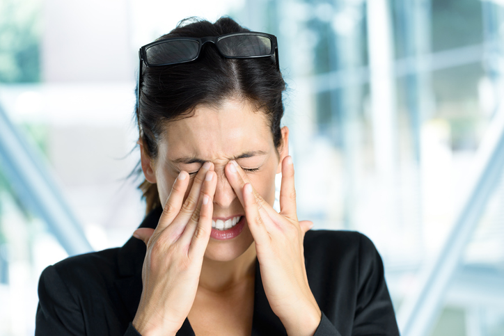 Business woman rubbing tired eyes with glasses pushed up on her head