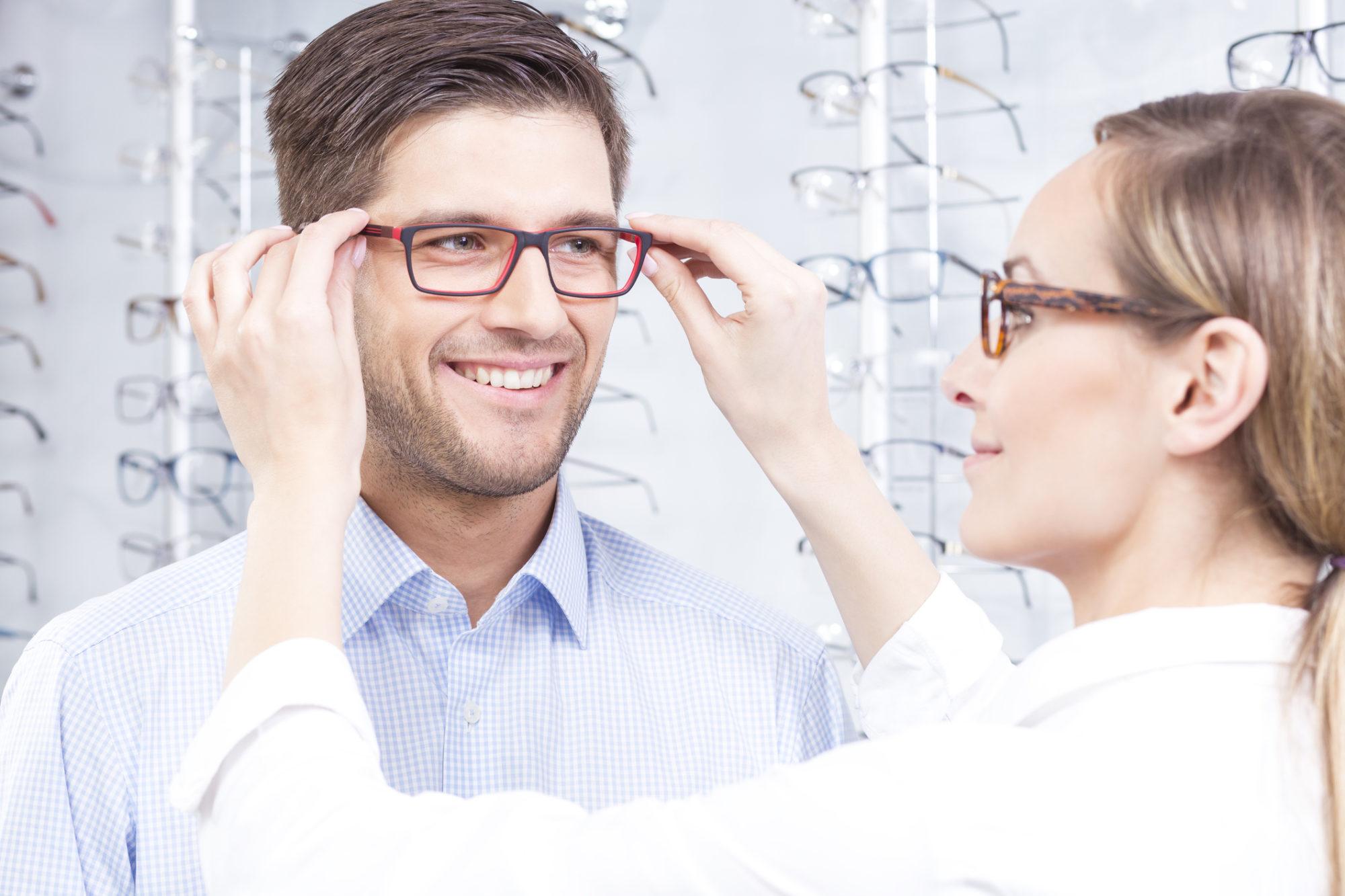 woman putting glasses on man in optical shop, optical shop Springfield MA, optometrist western MA